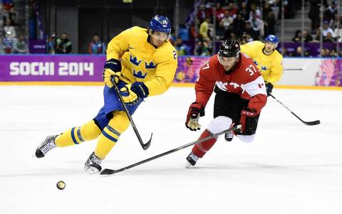 Sweden forward Loui Eriksson (21) controls the puck against Canada forward Patrice Bergeron (37) in the men's ice hockey gold medal game during the Sochi 2014 Olympic Winter Games at Bolshoy Ice Dome.