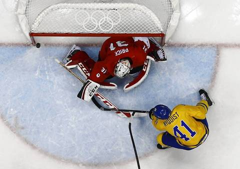Sweden's Gustav Nyquist (R) hits the post with a shot on Canada's goalie Carey Price during the first period of their men's ice hockey gold medal game at the Sochi 2014 Winter Olympic Games.