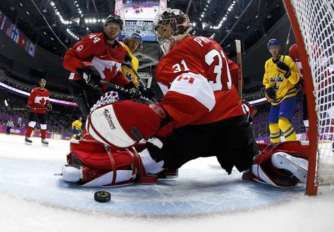 Canada's goalie Carey Price reaches back to glove a loose puck as Canada's Marc-Edouard Vlasic looks on during their men's ice hockey gold medal game against Sweden at the Sochi 2014 Winter Olympic Games.