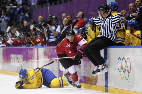 Canada forward Chris Kunitz (14) checks Sweden forward Marcus Kruger (16) in the men's ice hockey gold medal game during the Sochi 2014 Olympic Winter Games at Bolshoy Ice Dome.