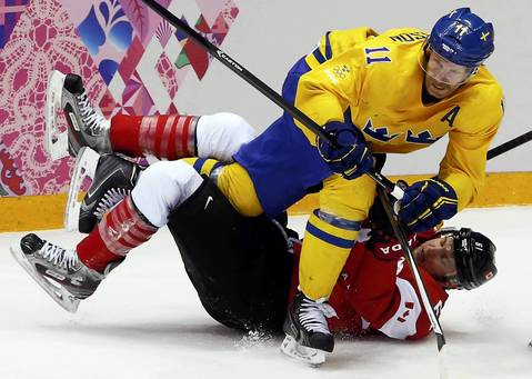 Canada's Rick Nash is checked by Sweden's Daniel Alfredsson (top) during the second period of their men's ice hockey gold medal match at the Sochi 2014 Winter Olympic Games.
