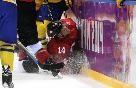 Chris Kunitz #14 of Canada crashes into the boards during the Men's Ice Hockey Gold Medal match against Sweden on Day 16 of the 2014 Sochi Winter Olympics at Bolshoy Ice Dome.
