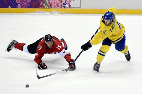 Sweden defenseman Niklas Hjalmarsson (4) takes a shot against Canada forward Ryan Getzlaf (15) in the men's ice hockey gold medal game during the Sochi 2014 Olympic Winter Games.