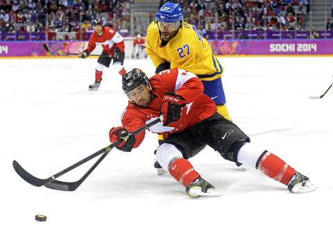 Patrice Bergeron #37 of Canada reaches for the puck against Johnny Oduya #27 of Sweden during the Men's Ice Hockey Gold Medal match.