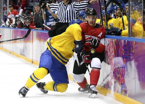 Niklas Hjalmarsson #4 of Sweden checks Jonathan Toews #16 of Canada into the boards during the Men's Ice Hockey Gold Medal match on Day 16 of the 2014 Sochi Winter Olympics at Bolshoy Ice Dome.