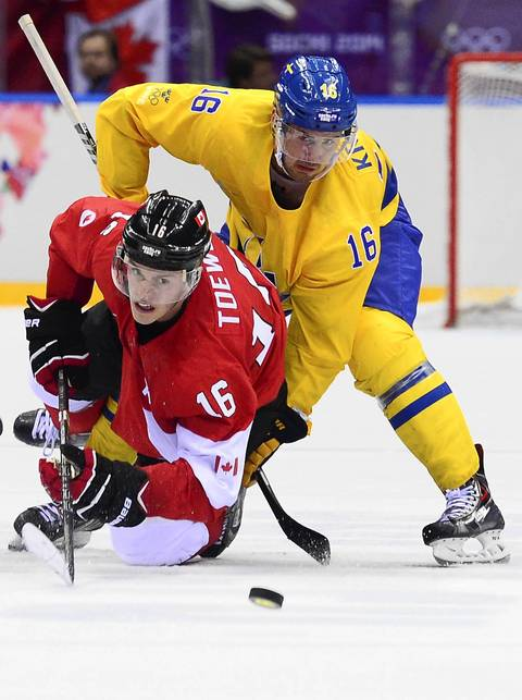 Sweden's Marcus Kruger (R) vies with Canada's Jonathan Toews during the Men's ice hockey final Sweden vs Canada at the Bolshoy Ice Dome during the Sochi Winter Olympics.
