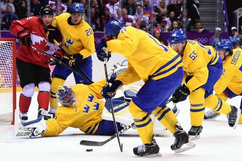Sweden's Daniel Alfredsson (C) and Sweden's Niklas Kronwall (2nd R) stop the puck during the Men's ice hockey final Sweden vs Canada at the Bolshoy Ice Dome during the Sochi Winter Olympics.