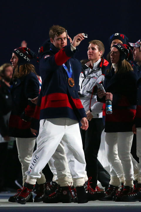 Gus Kenworthy of the United States enters the arena during the 2014 Sochi Winter Olympics Closing Ceremony.