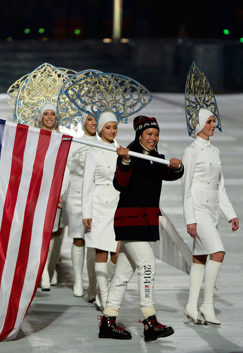 Hockey player Julie Chu of the United States enters with the flag during the 2014 Sochi Winter Olympics Closing Ceremony.