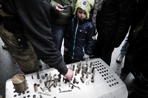 A child looks at empty bullet casings used by riot police during the past weeks' clashes in central Kiev.