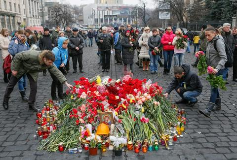 Ukrainians lay flowers and light candles in memory of those who were killed during the recent violent protests.