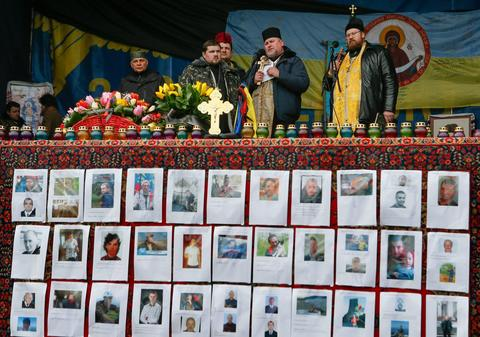 Ukrainian priests pray in memory of those who were killed during the recent violent protests in Kiev.