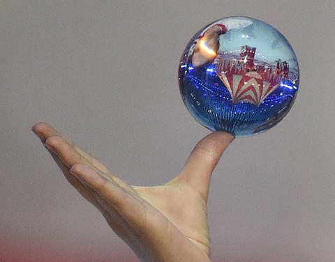 A scene of the 2014 Sochi Winter Olympics Closing Ceremony is reflected in a glass ball held by a circus performer.
