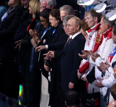 Russia President Vladimir Putin and President of the IOC, Thomas Bach, watch the 2014 Sochi Winter Olympics Closing Ceremony.