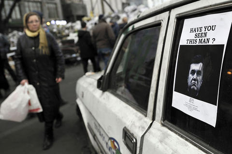 "A ""Wanted"" poster showing a portrait of ousted President Viktor Yanukovych is stuck on a car window in central Kiev on Feb. 24. Ukraine issued an arrest warrant for ousted president Yanukovych as the country's new rulers launched a probe over the ""mass murder"" of protesters in a week of carnage in Kiev."
