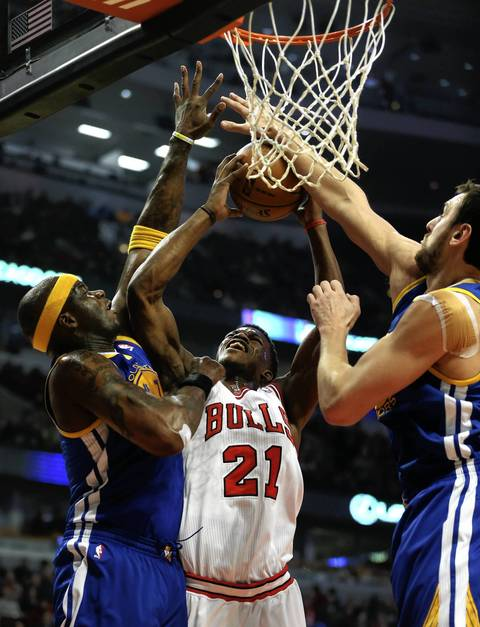 Jimmy Butler tries to put up a shot against Golden State's Jermaine O'Neal and Andrew Bogut in the first half.