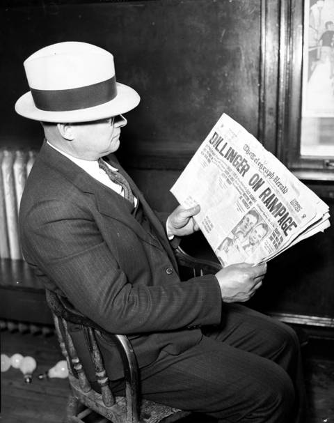 "Sgt. Edward A. Grim of the North Robey Street police station with a Dubuque, Iowa newspaper found in John Dillinger's stolen and abandoned automobile on May 2, 1934. The bloodstained getaway car, found at 3338 N. Leavitt Street in Chicago, had a surgical kit, matches from the Little Bohemia Resort, and the newspaper dated April 23, 1934 with the headline ""Dillinger On Rampage."""