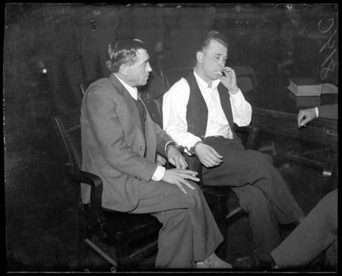 John Dillinger is handcuffed and guarded as he smokes during a court recess while Deputy Sheriff R. M. Pierce, left, looks on during Dillinger's hearing at Crown Point, Indiana in the first weeks of February 1934. Dillinger was charged with killing police officer William O'Malley, 43, during a bank robbery in East Chicago, Indiana on Jan. 15, 1934. His trail date was set for March 12, 1934. Dillinger would break out of the Crown Point, Indiana jail on March 3, 1934.