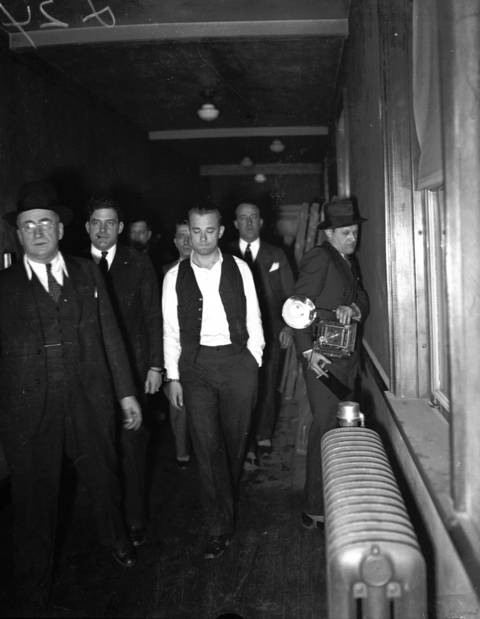 John Dillinger, center, is led through the Crown Point, Indiana court building on Jan. 31, 1934 to be viewed by witnesses from the First National Bank robbery that occurred on Jan. 15, 1934 in East Chicago, Indiana. Dillinger had been caught in Arizona and flown back to Indiana to be tried for the murder of patrolman William O'Malley, 43.
