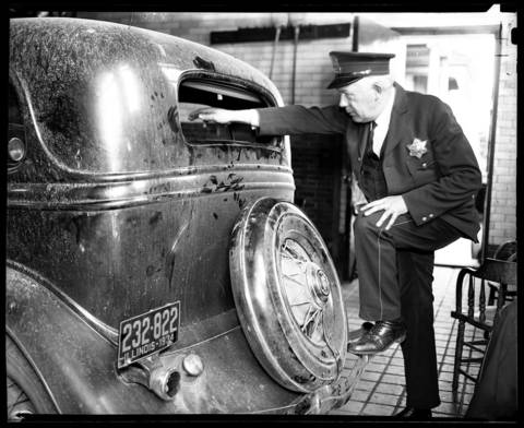 """A police officer shows the busted out rear window of John Dillinger's stolen and then abandoned automobile at the North Robey Street police station on May 2, 1934. The bloodstained Ford V-8 sedan, found at 3338 N. Leavitt Street in Chicago, had a surgical kit, matches from the Little Bohemia Resort, and a Dubuque, Iowa, newspaper dated April 23, 1934 with the headline """"Dillinger On Rampage."""""""
