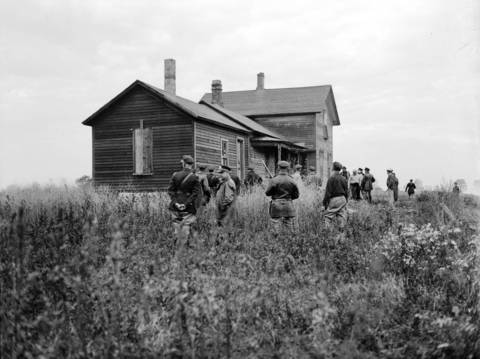 "Indiana state police surround the house where two of the convicts were supposed to have been from the Michigan City prison break, circa Oct. 1933. On Sept. 26, 1933, ten convicts, lead by John 'Red' Hamilton, broke out of the Indiana State Prison in Michigan City, Indiana, using guns smuggled to them by John Dillinger. In the coming days after the prison break, the Chicago Tribune reported over ""500 vigilantes, police and deputy sherriffs"" searched the farming districts near Michigan City for the felons. Dillinger, who was in a jail cell in Lima, Ohio, engineered the escape of the ten convicts, who became known as Dillinger's gang. Less than a month after they escaped from Michigan City, several of Dillinger's gang broke him out of the jail in Lima, Ohio."