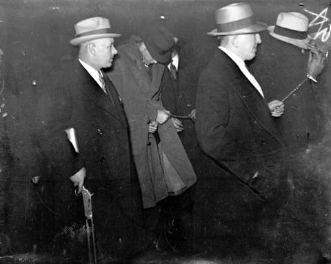 John Dillinger and his gang arrive in Chicago on Jan. 30, 1934 after their arrest in Arizona five days earlier. Dillinger had been caught in Arizona and flown back to Indiana to be tried for the murder of patrolman William O'Malley, 43. O'Malley was shot down during the First National Bank robbery in East Chicago, Indiana. Dillinger's trail date was set for March 12, 1934. Dillinger would break out of the Crown Point, Indiana jail on March 3, 1934.