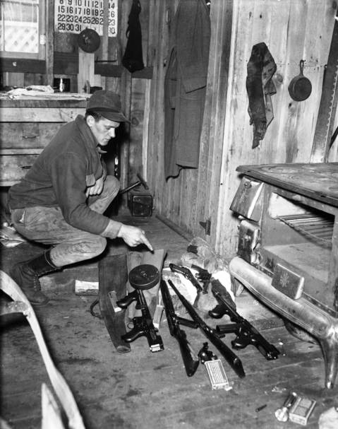 Max Organist looks at the guns left behind by John Dillinger and his gang on April 22, 1934 at the Little Bohemia Resort in Manitowish Waters, Wisconsin. FBI agents had surrounded the lodge were Dillinger and his gang were staying, but the outlaws were able to escape along the shore of the nearby lake.