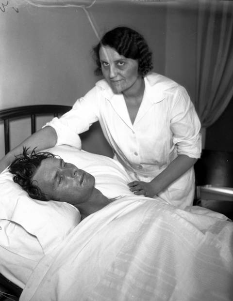 "Constable Carl C. Christensen with Mary Levendoski at the Twin City Hospital in Ironwood, Michigan after Christensen was shot by ""Baby Face"" Nelson of the John Dillinger gang during a gun fight at the Little Bohemia Resort in Manitowish Waters, Wisconsin on April 22, 1934. Christensen, a Spider Lake, Wisc. constable, was said to be gravely wounded but survived his wounds."