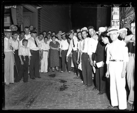 "People stand around the blood stain from John H. Dillinger, 32, in the alley behind the Biograph Theater in Chicago. Dillinger was shot and killed by FBI agents on July 22, 1934 after receiving a tip from Dillinger's friend Anna Sage. Sage, known as the ""Woman in Red,"" told authorities that she, Dillinger, and Dillinger's girlfriend Polly Hamilton Keele would be at the movies and to look for her dressed in red. Some reports say Sage was actually dressed in orange."