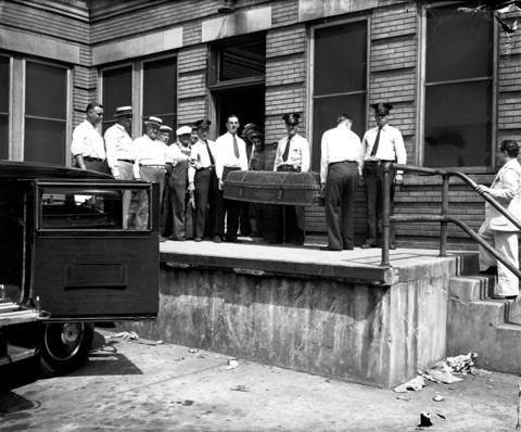 John Dillinger's body leaves the Cook County Morgue at Polk and Wood Streets to be taken to McCready Funeral home at 4506 Sheridan Road on July 24, 1934. Dillinger's father, John Dillinger Sr., 70, traveled from Mooresville, Ind. to claim his son's body. Dillinger was embalmed and then taken back to Indiana for burial.