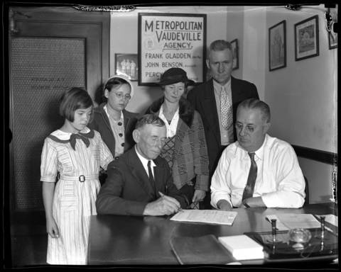 "John Dillinger Sr., seated (the father of notorious gangster John Dillinger), signs a contract to appear at the Walk-a-thon at Calumet City, Ill., while Frank Gladdin, general manager of the Metropolitan Vaudeville Agency, watches at the Woods Theater building on Aug. 28, 1934. With Dillinger Sr. are, from left, Frances Dillinger, 12, Doris Dillinger, 16 (both step-sisters of John Dillinger Jr.), Mrs. Audrey Hancock, (John Dillinger Jr.'s sister), and her husband Mr. Emmett Hancock. The Dillinger family, along with John Jr.'s girlfriend Evelyn ""Billie"" Frechette, toured with a theatrical production called ""Crime Doesn't Pay"" after Dillinger's death."