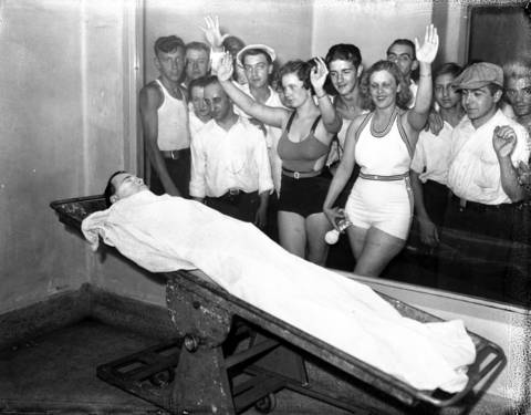 Betty Nelson and Rosella Nelson view the body of John Dillinger, 32, while in bathing suits at the Cook County Morgue, located at Polk and Wood Streets, in Chicago. In the days after Dillinger was killed on July 22, 1934, massive crowds lined up outside the morgue to get a glimpse of the notorious public enemy.