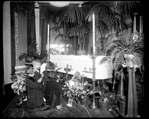 Three children kneel and pray in front of Wanda Stopa's casket on April 28 or 29, 1924. Stopa's family held the wake for Wanda in their apartment at 1505 W. Augusta Street on April 28, 1924. Her funeral, on April 29, 1924, was mobbed by curious onlookers as her body was taken to the Bohemian National Cemetery for burial.