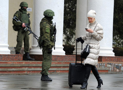 Unidentified armed men patrol outside of Simferopol airport in Crimea.