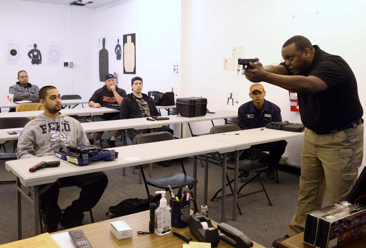 Instructor Andre Queen works with students on proper technique for holding their gun during a training course in 2013 for people planning to apply for a conceal carry permit.