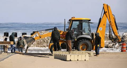 A crew uses a front-end loader to clear the area.