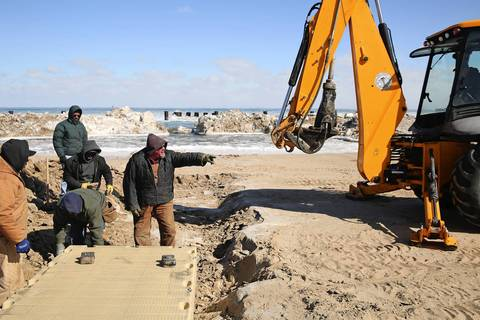 Workers place the walkway from the beach to the water.