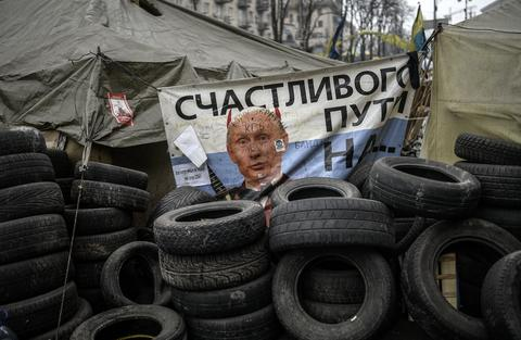 Russian President Vladimir Putin is seen on a banner at a barricade in central Kiev.