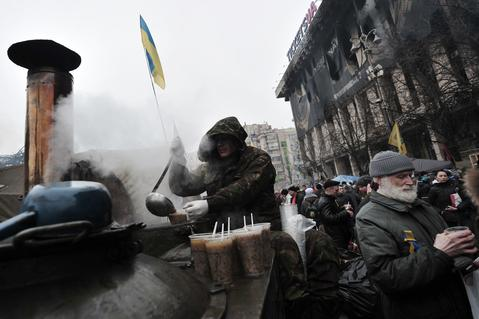 A so-called Maidan protester (C) serves hot soup to people on Independence square in central Kiev.