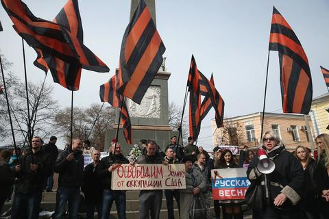 "Pro-Russian sympathizers wave the orange and black colors of Russian military valor as one man holds a sign that reads: ""We will free Ukraine from American occupation"" at an anti-American rally hours after heavily-armed, unidentifed soldiers took up positions around the nearby Crimean Parliament."