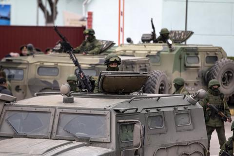 Armed servicemen stand in Russian army vehicles outside a Ukrainian border guard post in the Crimean town of Balaclava.