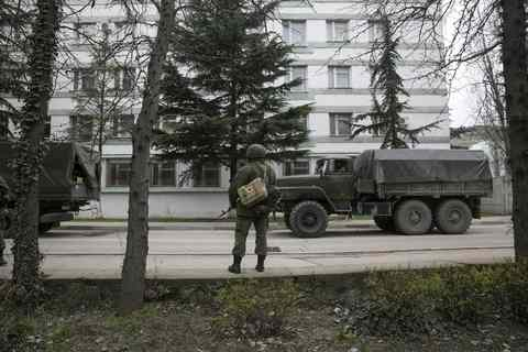 An armed serviceman stands near Russian army vehicles outside a Ukrainian border guard post in the Crimean town of Balaclava.