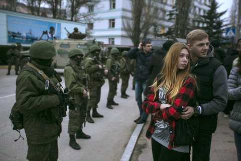 A couple stands next to armed servicemen outside a Ukrainian border guard post in the Crimean town of Balaclava.