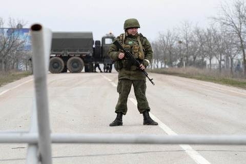 Armed servicemen stand on guard at a roadblock at the Belbek airport near Sevastopol.