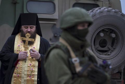 An Orthodox monk prays next to armed servicemen near Russian army vehicles outside a Ukrainian border guard post in the Crimean town of Balaclava.