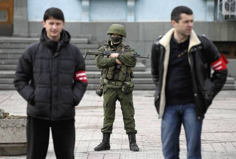 Heavily armed troops displaying no identifying insignia and local pro-Russian militants stand guard outside a local government building March 2, in Simferopol, Ukraine.