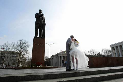 Newlyweds kiss near a statue of Lenin in the Crimean city of Simferopol.