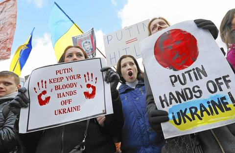 People protesting against Russian troops in Ukraine gather outside an European Union emergency foreign ministers meeting in Brussels.