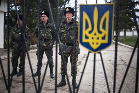 Ukrainian military men stand inside the territory of a Ukrainian military unit in the village of Perevalnoye, outside Simferopol, Ukraine.