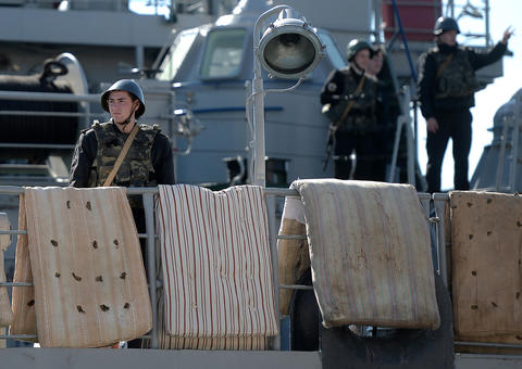 Ukrainian soldiers onboard the navy ship Slavutich look out at Russian forces patrolling in the harbor of the Ukrainian city of Sevastopol. The Ukrainian soldiers hung mattresses on the edge of the navy ship's railing to prevent Russian forces from forcefully boarding the ship with grappling hooks.